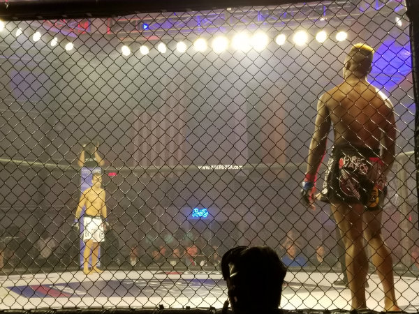 "Caio Rocha and Peter ""The Joker"" Petties mean mug one another from across the Titan FC cage."